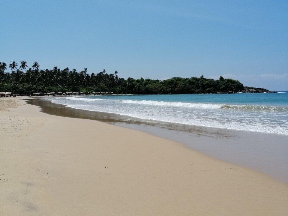 immagine di una lunga spiaggia bianca deserta