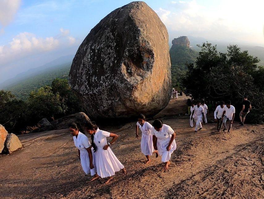 Pidurangala rock e studentesse vestite di bianco a piedi scalzi